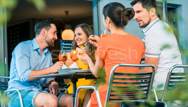 Cheerful friends toasting with a refreshing summer drink at a tr Stock photo © Kzenon