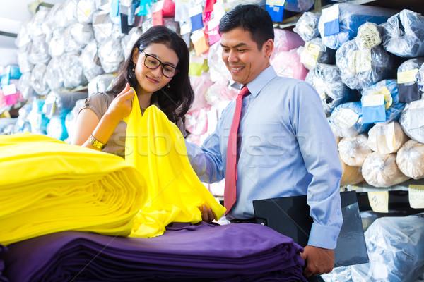 Asian colleagues in a warehouse choosing cloths Stock photo © Kzenon