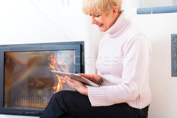 Female Senior at home in front of fireplace Stock photo © Kzenon