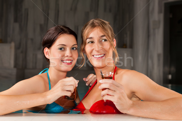Two female friends drinking tea in swimming pool Stock photo © Kzenon