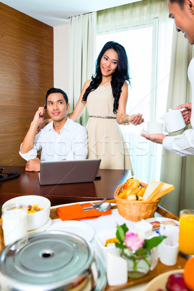 Asian room service waiter serving in hotel room Stock photo © Kzenon