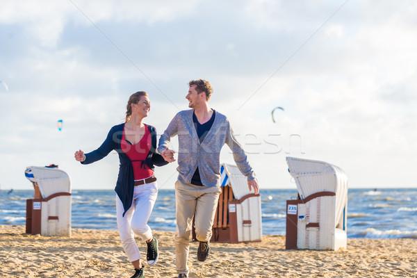 Couple at romantic sunset on beach Stock photo © Kzenon