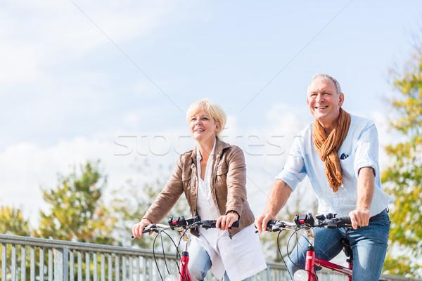 Senior couple with bicycles on bridge Stock photo © Kzenon