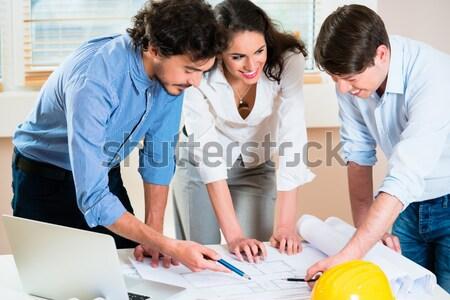 Architects bent over construction plans Stock photo © Kzenon