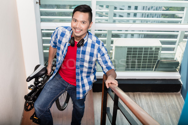 Young asian man carrying folding bike up the stairs to apartment Stock photo © Kzenon