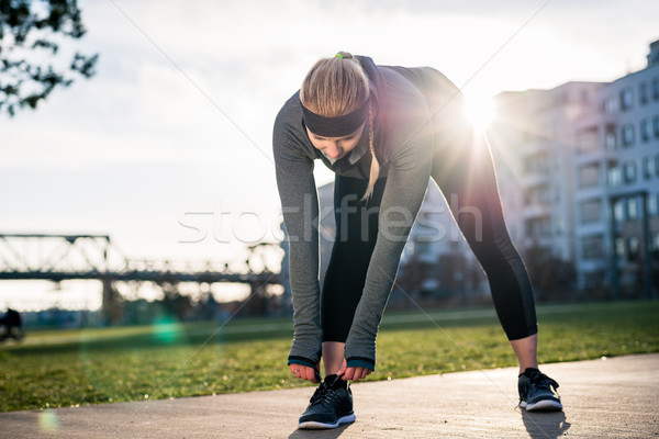Woman looking at camera with a smile while tying the shoelaces o Stock photo © Kzenon