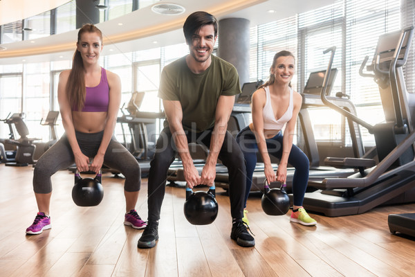 Three fit young people exercising kettlebell swings during full- Stock photo © Kzenon
