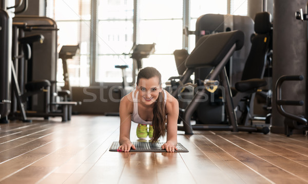 Young fit woman practicing the forearm plank exercise for core s Stock photo © Kzenon