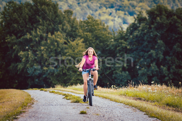 Girl on bicycle cycling down a dirt path in summer Stock photo © Kzenon