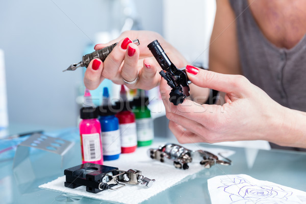 Close-up of the hands of a female artist preparing a professional tattoo machine Stock photo © Kzenon