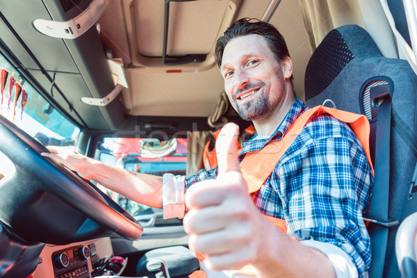 Truck driver sitting in cabin giving thumbs-up Stock photo © Kzenon