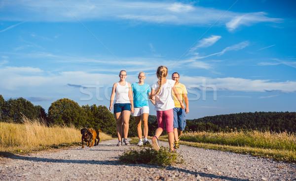 Family walking their dog on a dirt path Stock photo © Kzenon