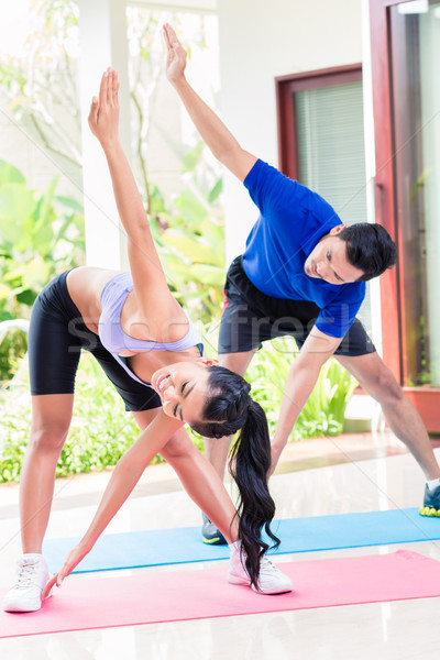 Asian man and woman in fitness exercise at home Stock photo © Kzenon