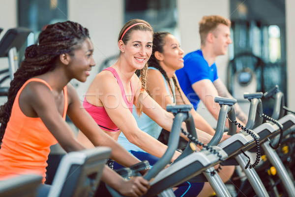 Side view of a beautiful woman smiling while cycling during spinning class Stock photo © Kzenon