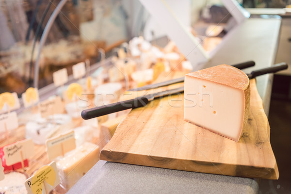 Cheese on a board at counter in delicatessen shop Stock photo © Kzenon