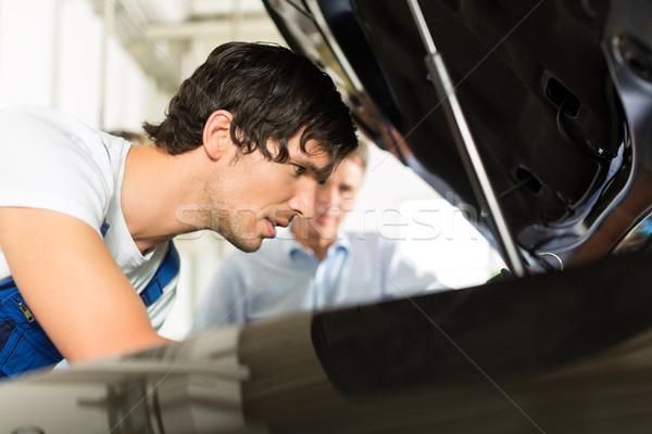 man and car mechanic looking beneath a hood Stock photo © Kzenon
