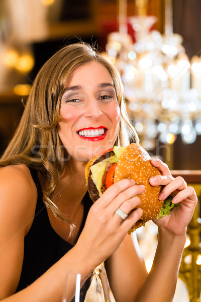 Young woman in fine restaurant, she eats a burger Stock photo © Kzenon