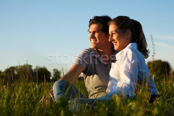 Couple on meadow in sunset Stock photo © Kzenon