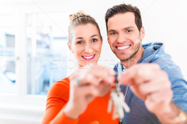 Woman and man holding proudly home or house key Stock photo © Kzenon