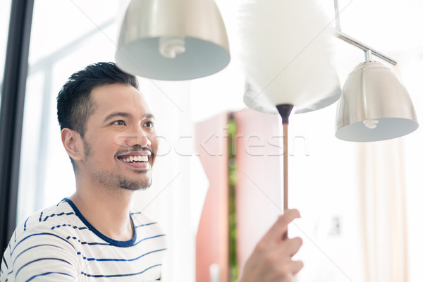 Asian man dusting his home Stock photo © Kzenon