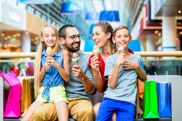 Family eating ice cream in shopping mall with bags Stock photo © Kzenon