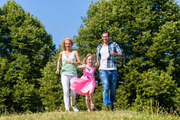 Mum, Dad and daughter running on a country lane Stock photo © Kzenon