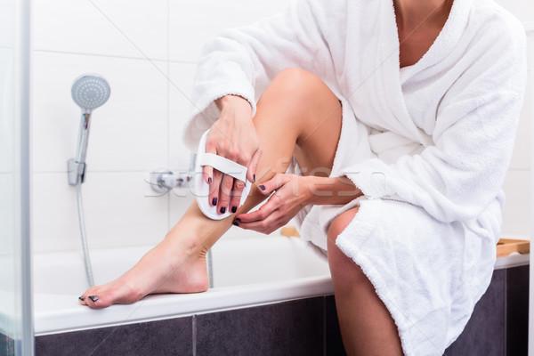 Woman applying peeling at her legs  Stock photo © Kzenon