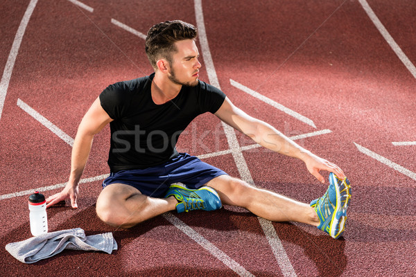 Athlete stretching on racing track before running Stock photo © Kzenon