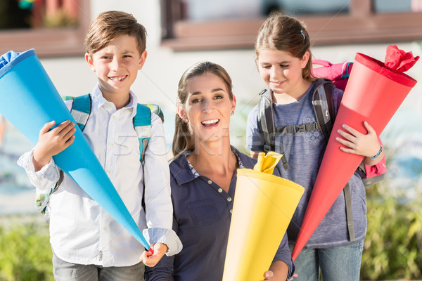 Mother and children on first day of school with candy cones Stock photo © Kzenon