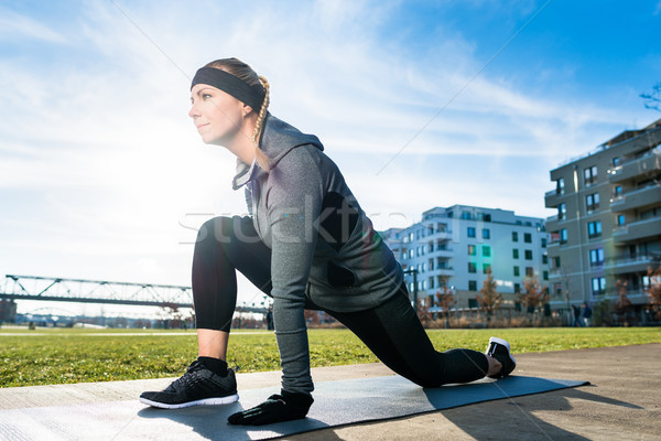 Determined young woman stretching her leg while kneeling on a ma Stock photo © Kzenon