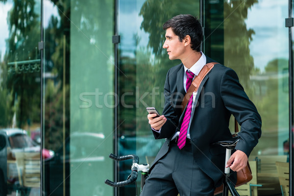 Young corporate employee holding a mobile phone while waiting ou Stock photo © Kzenon