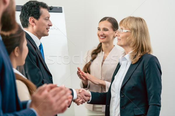 Stock photo: Two middle-aged business associates smiling while shaking hands