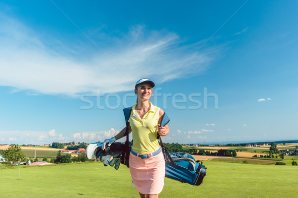 Full length rear view of an active woman carrying a blue stand bag Stock photo © Kzenon