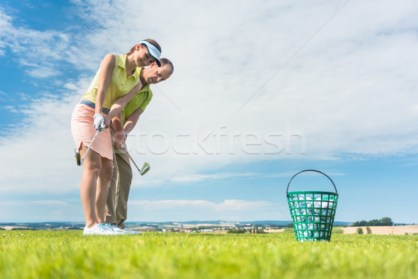 Young woman exercising the golf swing helped by her instructor Stock photo © Kzenon
