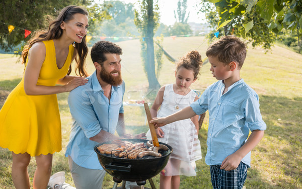 Father and son preparing meat on charcoal barbecue grill Stock photo © Kzenon