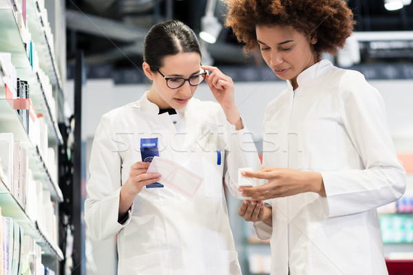 Reliable pharmacists analyzing a prescription and two different medicines Stock photo © Kzenon