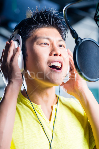 Asian male singer producing song in recording studio Stock photo © Kzenon
