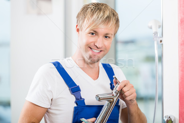 Portrait of a cheerful maintenance worker holding a faucet Stock photo © Kzenon