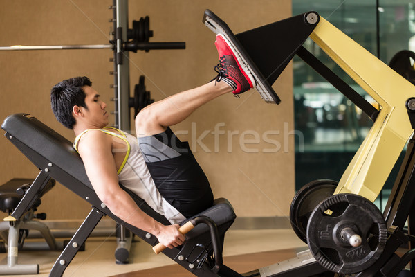 Young man exercising at the leg press during lower body workout  Stock photo © Kzenon