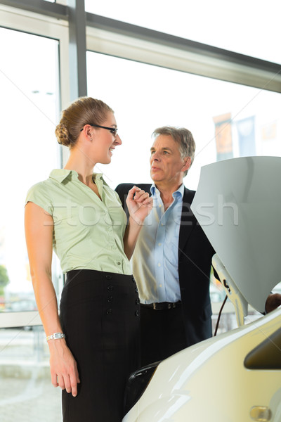 man and woman in car dealership looking under  a hood Stock photo © Kzenon