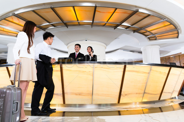 Asian Chinese couple arriving at hotel front desk Stock photo © Kzenon