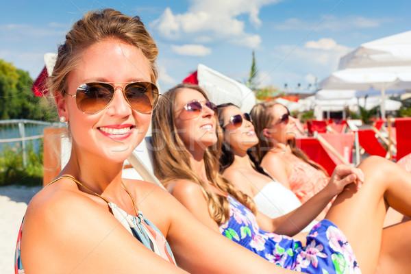 Friends tanning in beach bar Stock photo © Kzenon