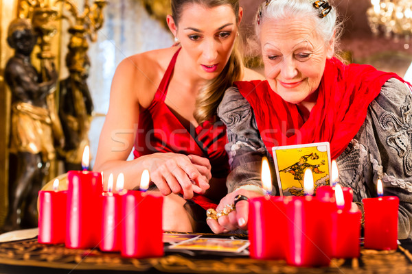 Fortuneteller laying Tarot cards with client Stock photo © Kzenon