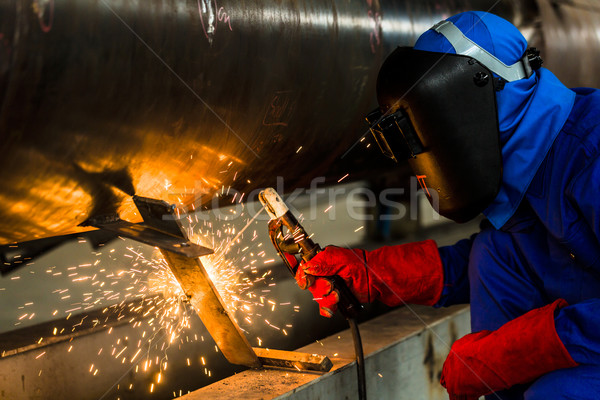 Welder in factory welding metal pipes Stock photo © Kzenon