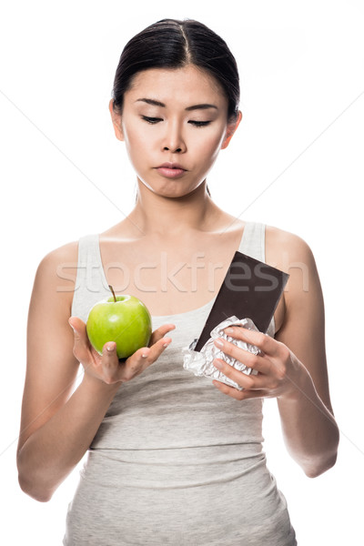 Pretty Asian woman debating an apple or chocolate Stock photo © Kzenon