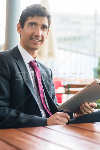 Young man wearing business suit while using a tablet PC during b Stock photo © Kzenon
