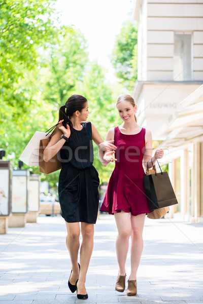 Stock photo: Two beautiful women looking for fashion boutiques during shoppin
