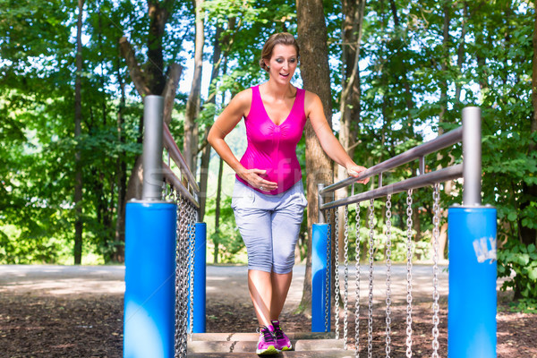 Pregnant woman doing fitness sport in climbing park Stock photo © Kzenon