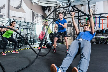 Men with battle rope in functional training fitness gym Stock photo © Kzenon