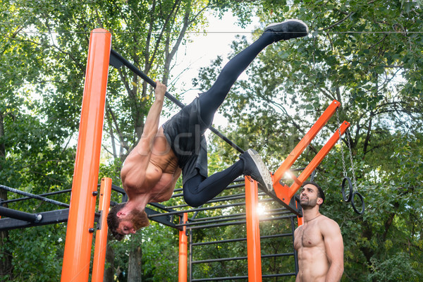 Shirtless bodybuilder hanging on horizontal bar during extreme w Stock photo © Kzenon